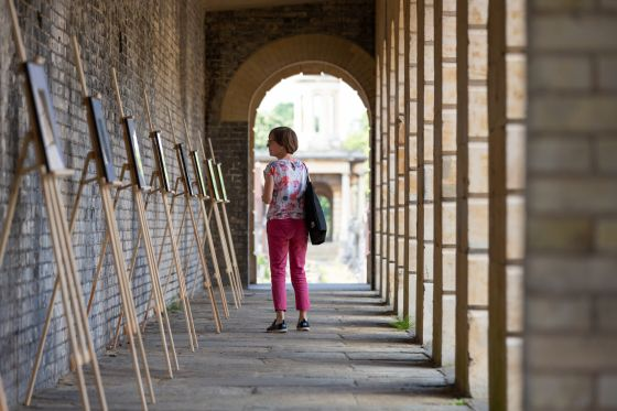 A woman looking at art on display at Brompton Cemetery