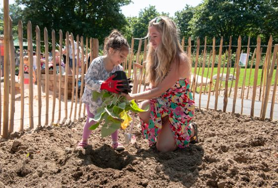 Play Coordinator Belle Benham gets help from a child to plant new flowers