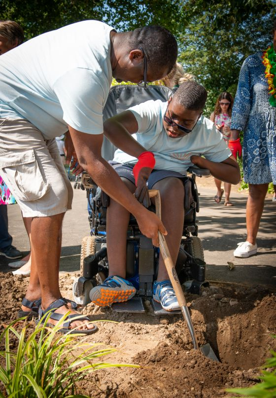 A boy in a wheelchair helps to dig the flower beds