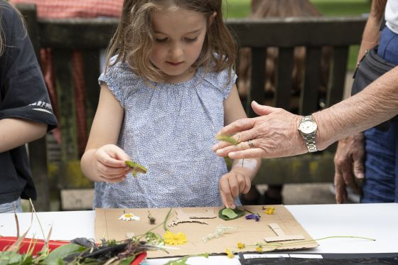 Girl using flowers and leaves to make beautiful art