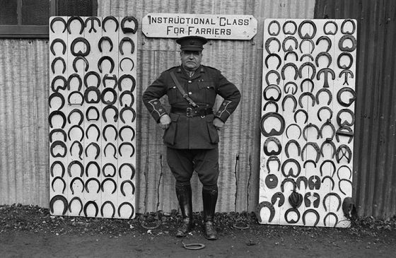 An older man stands in front of a sign for the Instructional Class for Farriers.